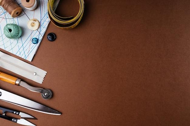 Composizione piatta di accessori per cucire, forbici, motivi su sfondo marrone, vista dall'alto, spazio per le copie. la scrivania di uno stilista, sarto in un atelier. concetto di cucito in stile vintage.