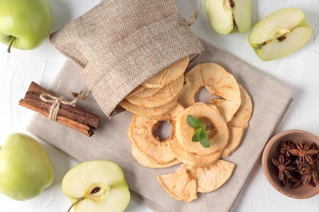 Composizione piatta laica con patatine di mele in un piccolo sacco sul tavolo bianco