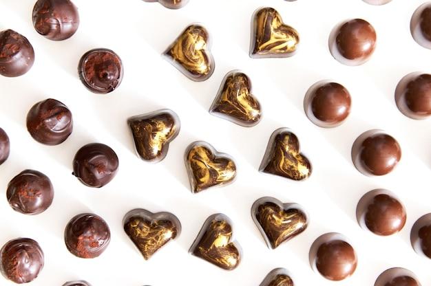 Composizione piatta con assortimento di cioccolatini belgi fatti a mano con ornamenti in oro e granelli di cacao in polvere su una superficie bianca.