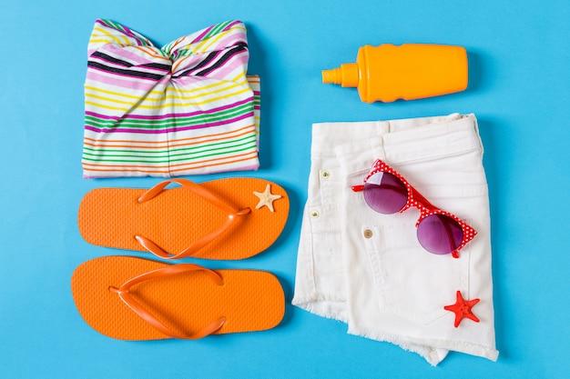 Composizione piatta con accessori da spiaggia di colore blu.