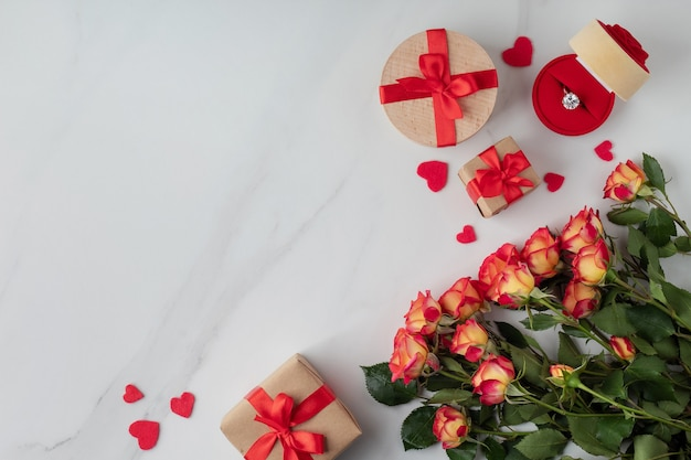 Composizione piatta con bellissimi fiori, scatole regalo e anello di fidanzamento sul tavolo di marmo