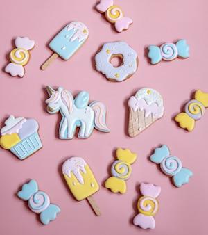 Composizione piatta con biscotti di panpepato smaltati luminosi su sfondo rosa.