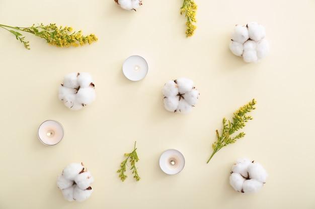 Composizione piatta con candele accese e bellissimi fiori su sfondo colorato