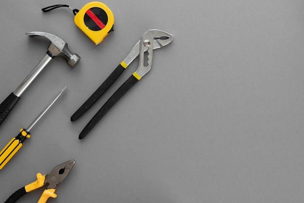 Composizione piatta con strumenti per la costruzione e la riparazione della casa su sfondo grigio, spazio per il testo