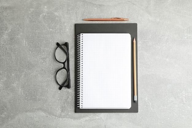 Composizione piatta laica con quaderno e occhiali, spazio per il testo