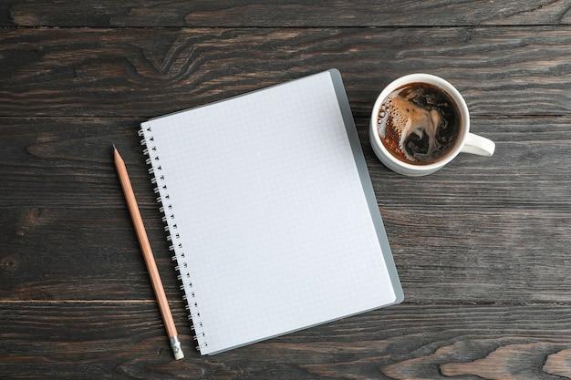 Composizione piatta laica con una tazza di caffè, quaderno e matita, spazio per il testo