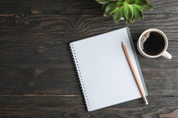 Composizione piatta laica con tazza di caffè, quaderno, matita e pianta succulenta, spazio per il testo