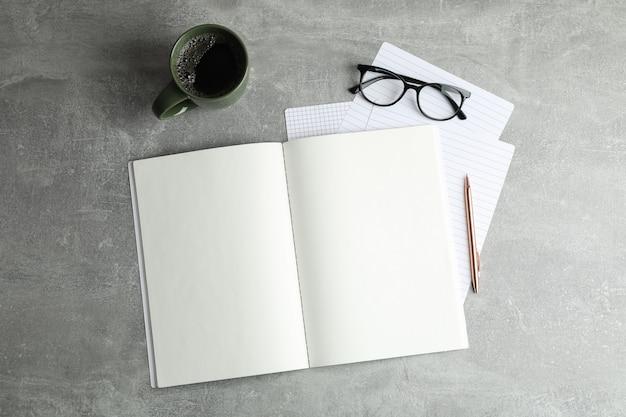 Composizione piatta laica con una tazza di caffè, quaderni e bicchieri, spazio per il testo