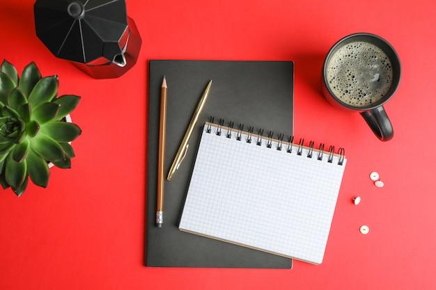 Composizione piatta laica con tazza di caffè, quaderni, matite e pianta succulenta, spazio per il testo