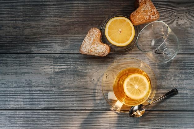 Composizione piatta laici con una tazza di tè, limone e muffin su un tavolo di legno
