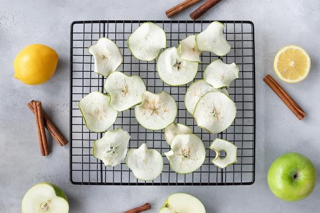 Composizione piatta con scaglie di mele disidratate, mele, limoni e bastoncini di cannella