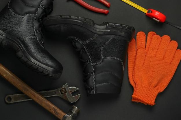 Composizione piatta con diversi strumenti e strumenti di lavoro industriali, equipaggiamenti di sicurezza su sfondo nero vista dall'alto