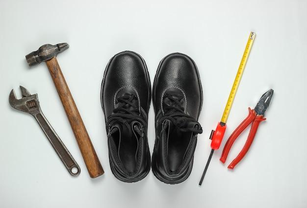 Composizione piatta laica con diversi strumenti e strumenti di lavoro industriale, equipaggiamenti di sicurezza su priorità bassa bianca. vista dall'alto