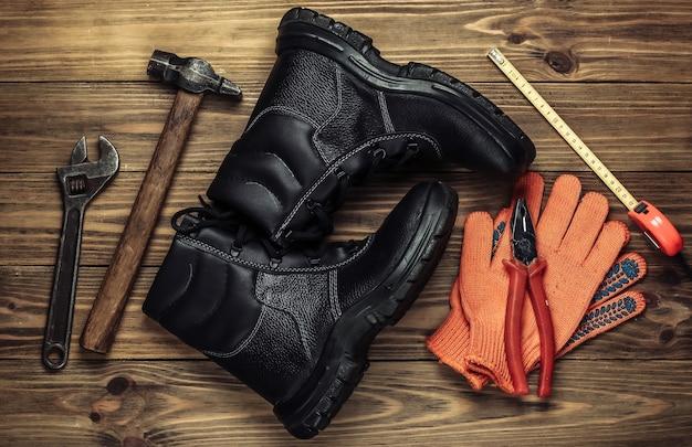 Composizione piatta laica con diversi strumenti e strumenti di lavoro industriali, equipaggiamenti di sicurezza su fondo in legno. vista dall'alto
