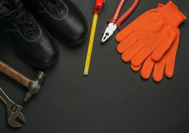 Composizione piatta con diversi strumenti e strumenti di lavoro industriali, equipaggiamenti di sicurezza su sfondo giallo. copia spazio. vista dall'alto