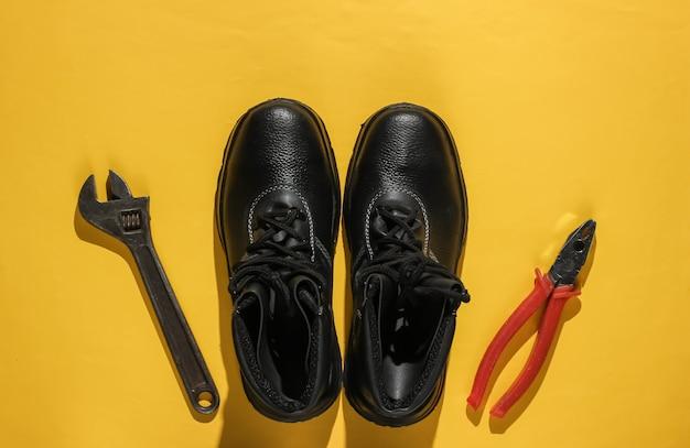 Composizione piatta con diversi strumenti e strumenti di lavoro industriali, equipaggiamenti di sicurezza su sfondo giallo. vista dall'alto