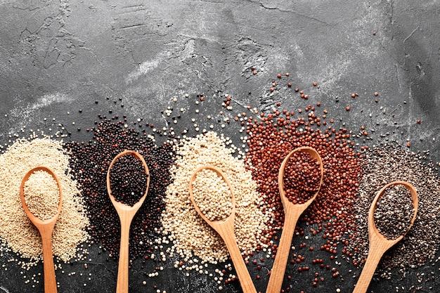 Composizione piatta con diversi tipi di quinoa su sfondo nero. vista dall'alto.