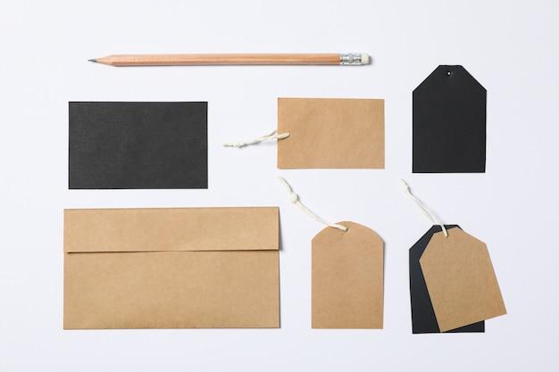 Composizione piatta laica con busta, etichette e matita su sfondo bianco