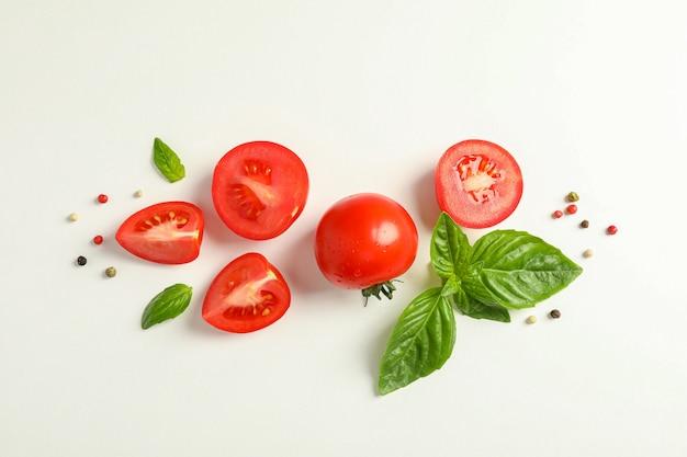 Composizione piatta laica con pomodorini freschi, pepe e basilico su spazio bianco, spazio per il testo. verdure mature