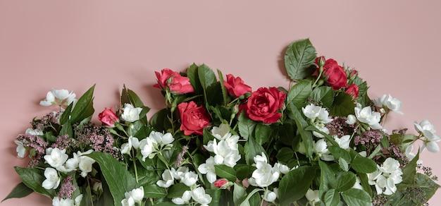 Composizione piatta laica con fiori freschi su sfondo rosa.