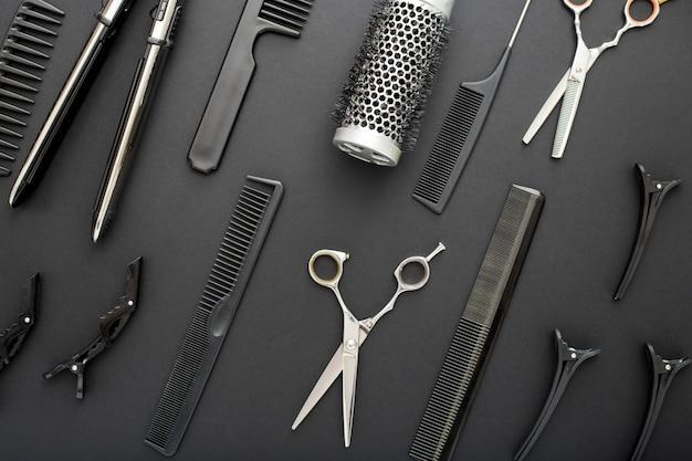 Composizione piatta con forbici strumenti parrucchiere, pettini, ferro per capelli sul nero