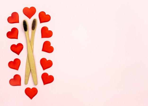 Composizione piatta laica con forma di cuori con spazzolini da denti di bambù e spazio per il testo sulla parete rosa, vista dall'alto. concetto di ecologia con uno stile di vita sano.