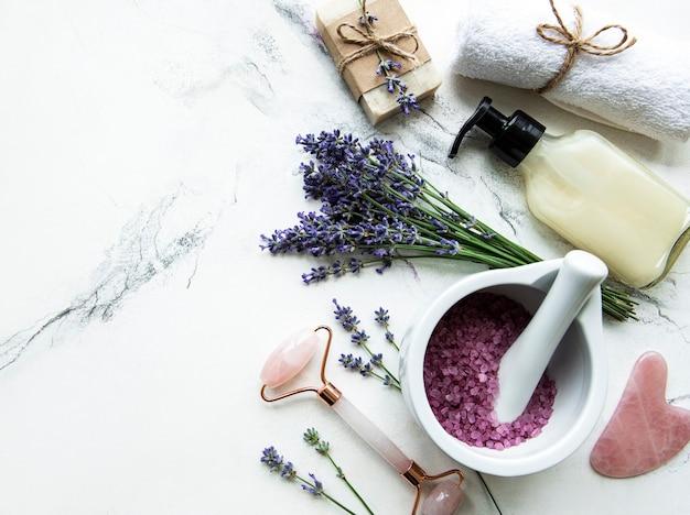 Composizione piatta con fiori di lavanda e cosmetici naturali su fondo in marmo