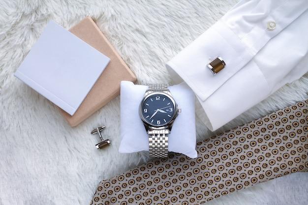 Composizione piatta con orologio da polso da uomo di lusso, cravatta, camicia e gemelli vista dall'alto