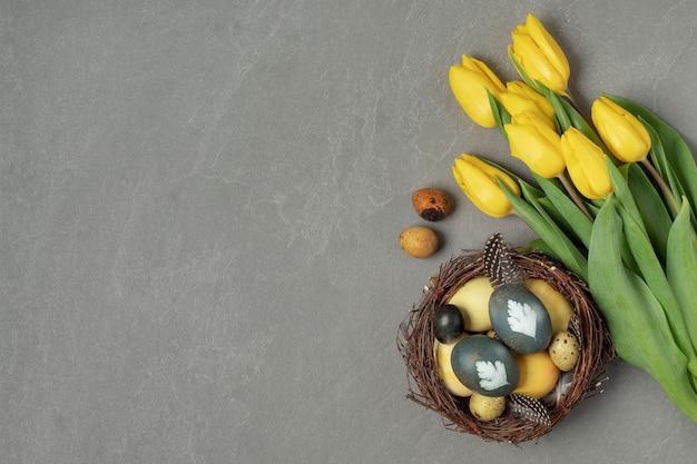Composizione piatta con uova di pasqua colorate naturalmente nel nido e tulipani gialli