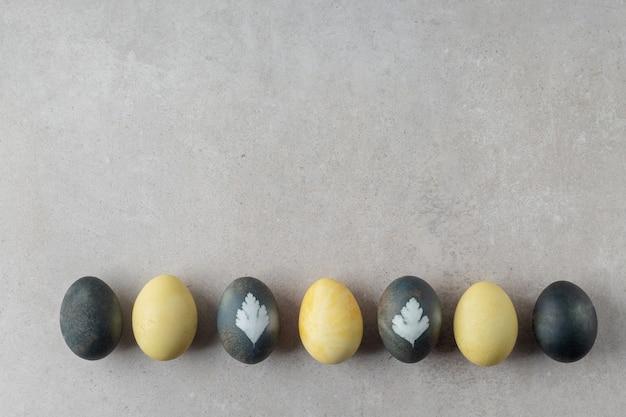Composizione piatta con uova di pasqua dipinte naturalmente sul tavolo grigio, spazio per il testo