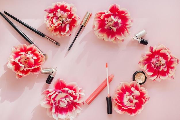 Composizione piatta con prodotti per il trucco decorativo su un tavolo rosa.