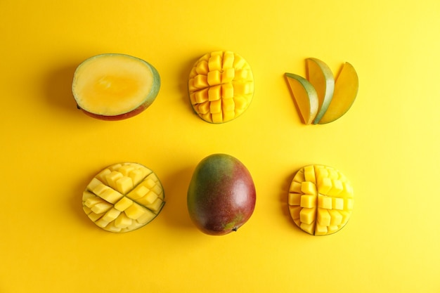 Composizione piatta con manghi maturi su sfondo colorato