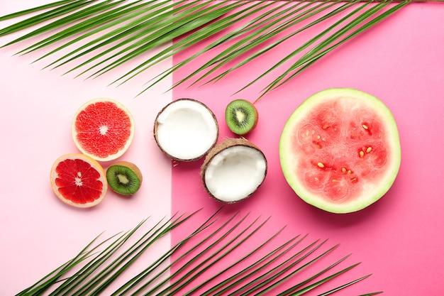 Composizione piatta laica con vari frutti deliziosi su rosa e bianco