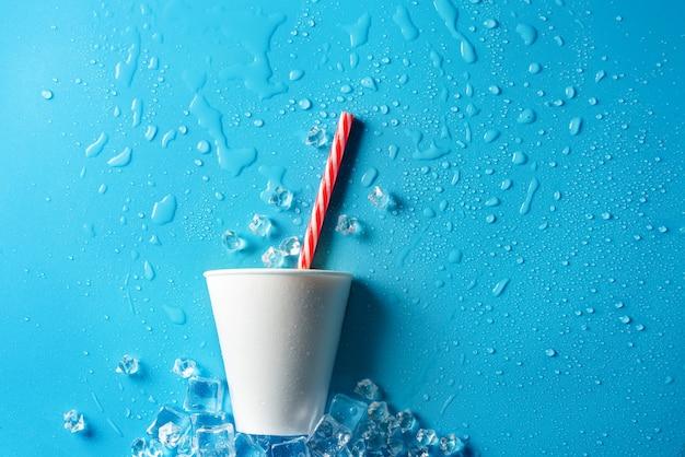 Composizione piatta con una tazza usa e getta bianca e una cannuccia su un blu bagnato.