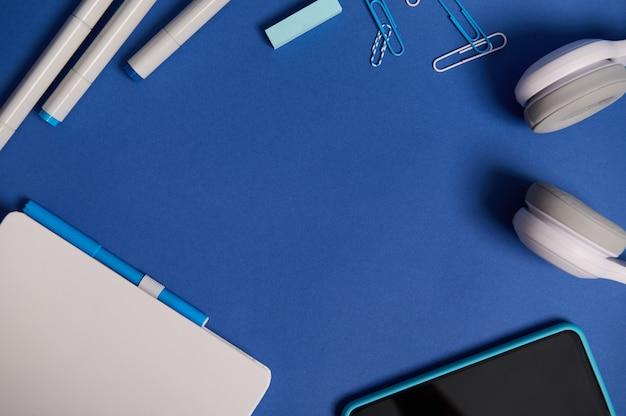 Composizione piatta con cancelleria bianca per ufficio o materiale scolastico e gadget elettronici wireless sparsi in un cerchio su sfondo blu con spazio per le copie. ritorno a scuola, concetto di festa dell'insegnante