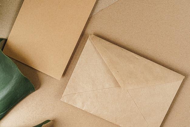 Mockup di carta di carta artigianale piatto laico con foglie, vista dall'alto