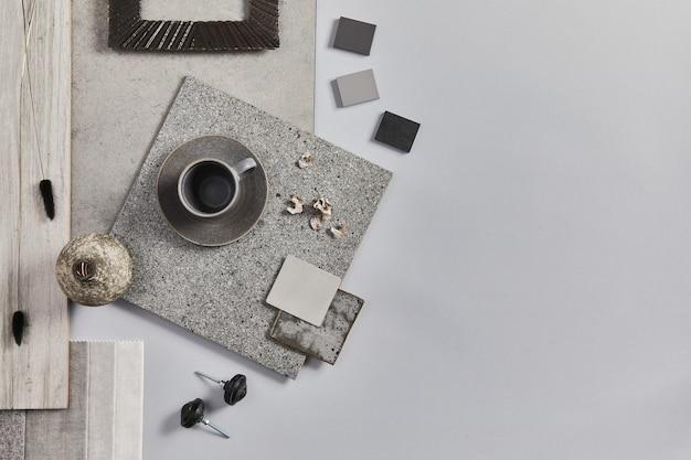 Disposizione piatta della composizione moodboard dell'architetto creativo con campioni di materiali edili, tessili e naturali e accessori personali. vista dall'alto, sfondo grigio, modello.