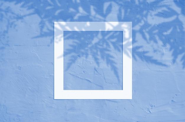 Disposizione piana di copyspace creativo con la struttura di carta e l'ombra tropicale della palma delle foglie. colore blu classico. colore dell'anno 2020.
