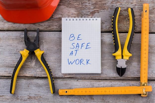 Accessori per cunstructor piatti e slogan sul lavoro sicuro. strati con righello e casco su tavola di legno.