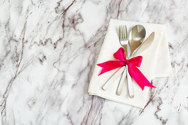 Piatto lay - posate, cucchiaio forchetta e coltello su un tovagliolo rustico e un fiocco di nastro di seta si trovano su uno sfondo di tavolo in marmo