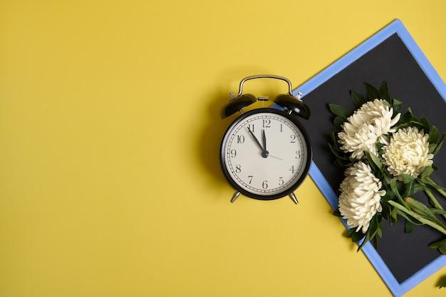 Disposizione piana di delicato bellissimo ed elegante bouquet di fiori autunnali di astri su una lavagna vuota vuota con spazio per il testo e una sveglia isolata su sfondo giallo