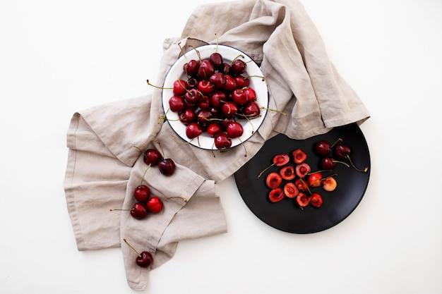Disposizione piatta di piatti con ciliegie su sfondo bianco
