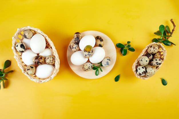 Composizione di pasqua piatta laici con foglie verdi e uova di pasqua su uno sfondo giallo, buona pasqua, copia spazio, vista dall'alto.