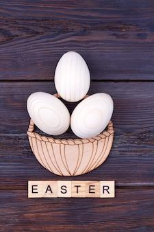 Piatto pasqua laici concetto. cesto di uova di gallina sul tavolo di legno scuro.