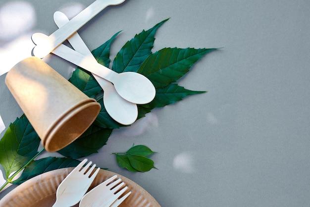 Disposizione piatta di carta ecologica e stoviglie in legno, rifiuti zero, vita senza plastica ed ecologica, bicchieri di carta, piatti, piatti e posate in legno, riciclaggio o concetto ecologico