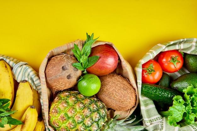 Disposizione piatta di sacchetti di cotone per la spesa di generi alimentari ecologici con frutta e verdura biologica su giallo