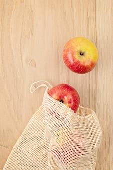 Disposizione piatta del sacchetto di cotone a rete riutilizzabile ecologico con mele. concetto di stile di vita sostenibile, etico, senza plastica e zero rifiuti. vista dall'alto