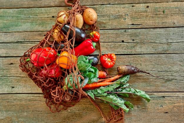 Borsa a rete riutilizzabile per lo shopping a corda ecologica piatta con assortimento di verdure fresche, cibo biologico sano e biologico su fondo in legno, stile mercato di campagna, drogheria, cibo vegetariano dietetico.