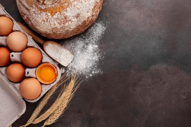 Disposizione piana del cartone dell'uovo con pane e farina