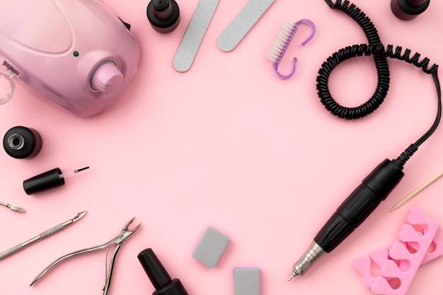 Attrezzatura piatta per manicure su sfondo rosa.
